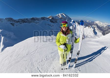Happy woman in mask standing and holding ski