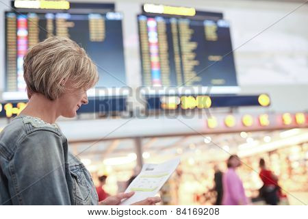 Woman tourist looking at timetable in airport