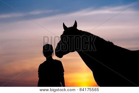 The girl near to a horse standing in front of a beautiful sunset. Silhouette of a woman and a horse