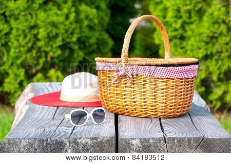 White Sunglasses Summer Hat And Wicker Basket On Wooden Table