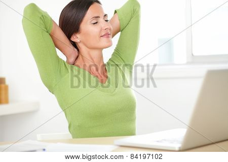 Elegant Hispanic Woman Resting On Desk