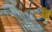 Construction worker compacting liquid cement in reinforcement form work during concreting floors pouring works poster