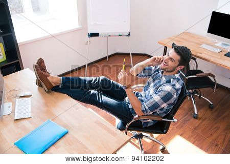 Happy relaxed businessman sitting on the office chair and talking on the phone in office