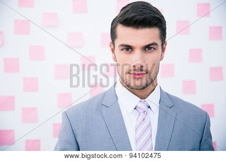 Portrait of a confident businessman standing in office and looking at camera