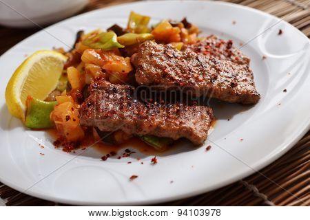 Adana kofte with roasted vegetables and lemon