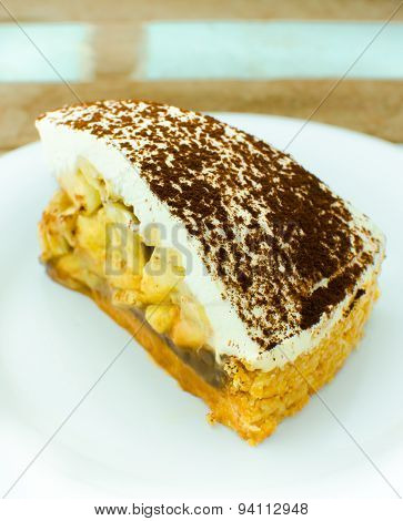 Banoffee pie on wooden plate in soft light