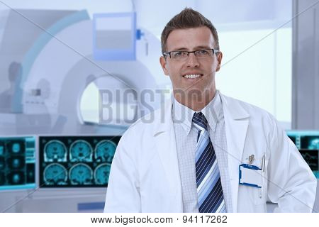 Portrait of mid-adult male doctor in MRI room at hospital, looking at camera, smiling.
