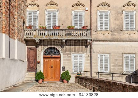 Facade of typical italian house with balcony and wooden door in town of La Morra in Piedmont, Northern Italy.