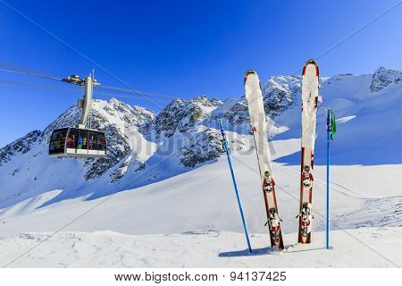 Skiing, winter season - mountains, cable car and ski equipments on ski run