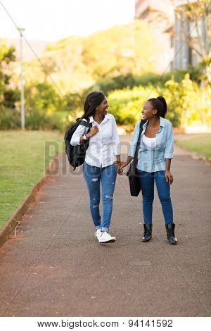 beautiful african american college students walking on modern campus