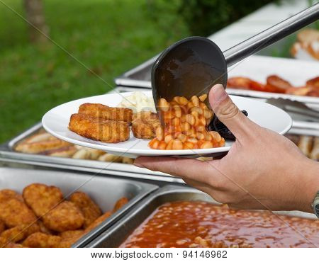 Hand With Plastic Ladle Serves Baked Beans And Nuggets