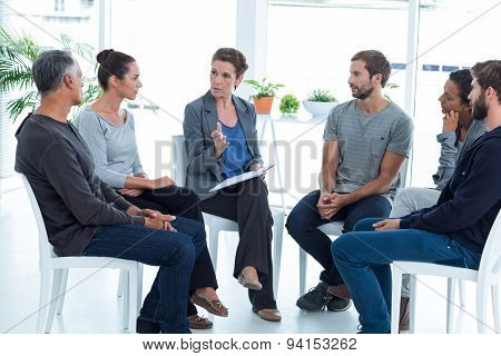 Group therapy in session sitting in a circle in a bright room