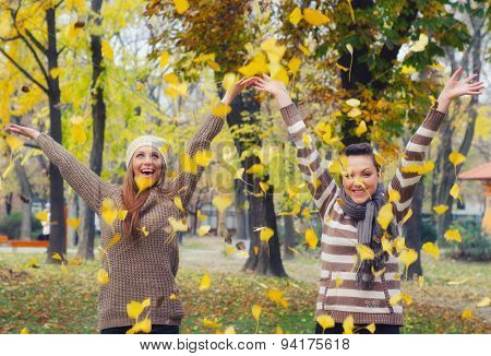 Two Beautiful Girls Throwing Leaves In The Air In Autumn Forest
