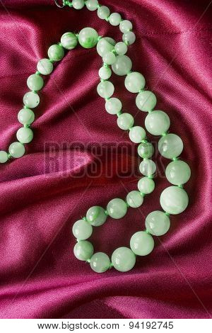 String of nephrite beads on red silk as a background poster