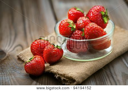 Bowl with fresh strawberries on a wooden ground