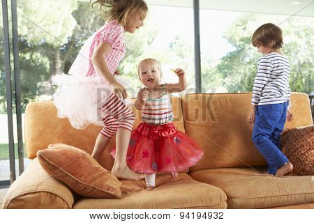 Group Of Children Jumping On Sofa