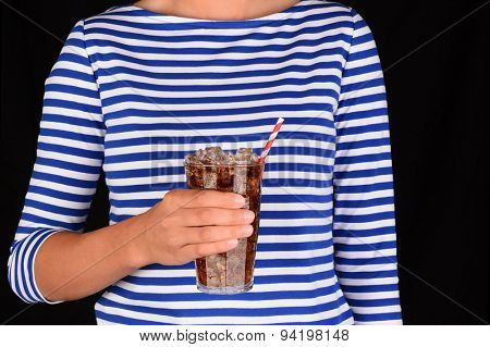 Closeup of a girl holding a cold glass of soda in front of her torso. A red a white striped straw is in the glass and the unrecognizable female is wearing a blue striped blouse.