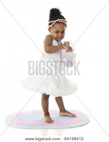 An adorable two year old looking bashful in her petticoat and pearls.  On a white background.