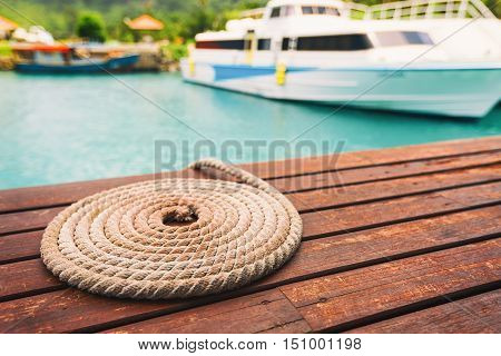 Rope folded in circle shape by the pier and speed boat on background