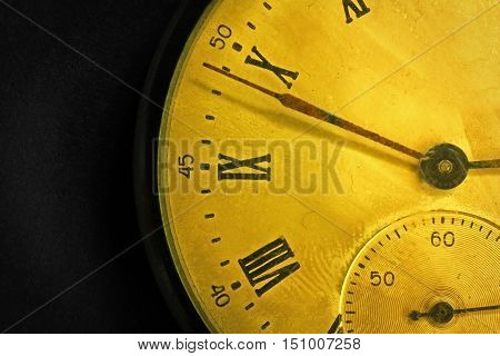 Tarnished clock face of old soviet pocket watch close up on dark background
