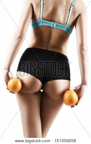 Beautiful female figure with an orange holds near the ass. studio shot on white background. white lace thong cellulite
