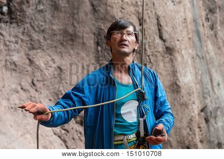 Mature Male Sport Coach belays climbing Athlete holding Rope and Belaying Device in sporty clothing staying on rocky terrain
