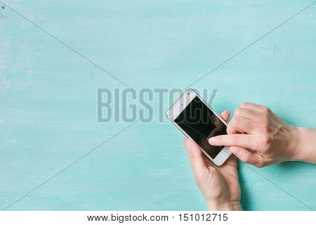 woman's hands with smartphone on turquoise background. Girl holding phone and typing. Communication concept