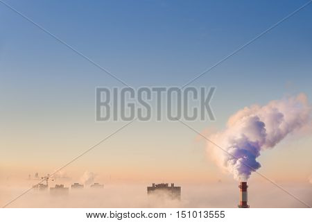 Smoking pipes of thermal power plant on sunset. White smoke and steam from a high chimney of a power plant against a bright blue sky. air pollution