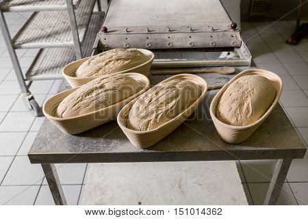 Raw fermented loaves of bread in a wicker basket ready in the oven. The concept of baking and pastry shops.