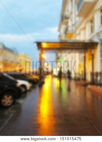 Blurred Bokeh Landscape City Streets In The Evening In Rainy Day. Blurred Background In Warm Dark Co