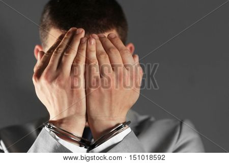 Man in handcuffs hiding face on grey background