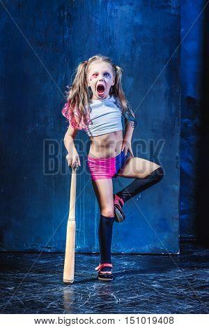 Halloween theme: Girl with baseball bat ready to hit on dark background