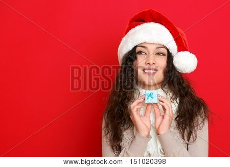girl in santa hat portrait with little gift box posing on red color background, christmas holiday concept, happy and emotions