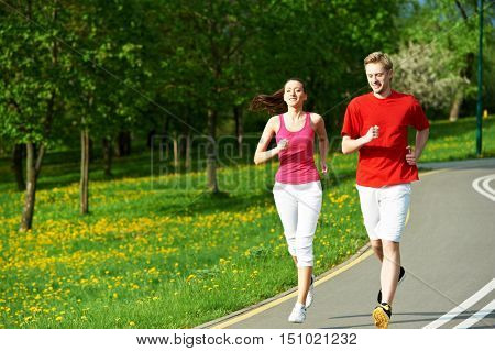 Young man and woman jogging outdoors