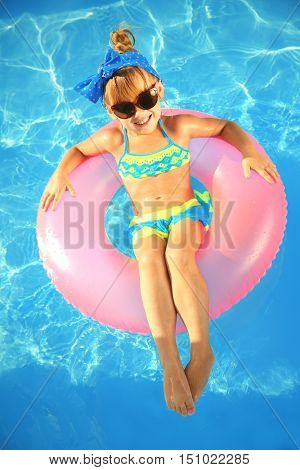 Little girl in swimming pool on sunny day