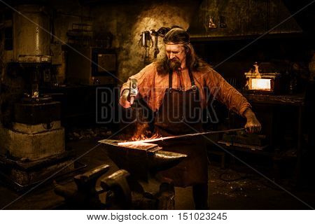 Senior blacksmith forging the molten metal on the anvil in smithy. poster
