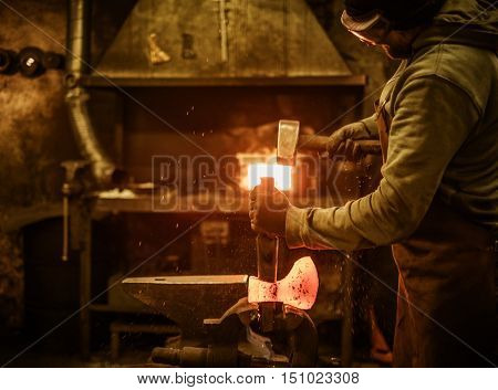 The blacksmith forging the molten metal on the rusty vise in smithy.