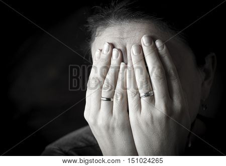 Portrait of a weeping woman. She covered her face with her hands.
