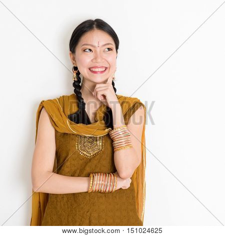 Portrait of thoughtful mixed race Indian Chinese girl in traditional punjabi dress is thinking, standing on plain white background.