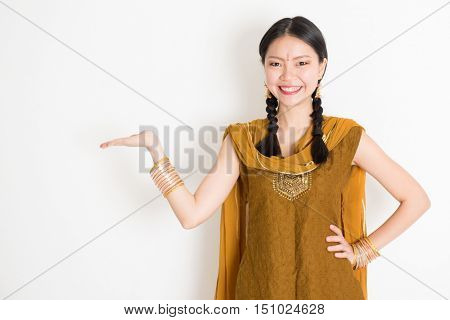 Portrait of young mixed race Indian Chinese female in traditional punjabi dress hand holding somethings, standing on plain white background.