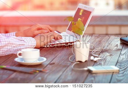 Casual dressed man sitting wooden desk outdoor patio working computer typing keyboard color pencils electronic gadgets green Plant Focus on hand and edge of Laptop