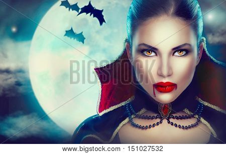 Halloween Vampire Woman portrait over scary night background. Beauty Sexy Vampire Girl with dripping blood on her mouth. Vampire makeup Fashion Art design. Model girl in Halloween costume and make up