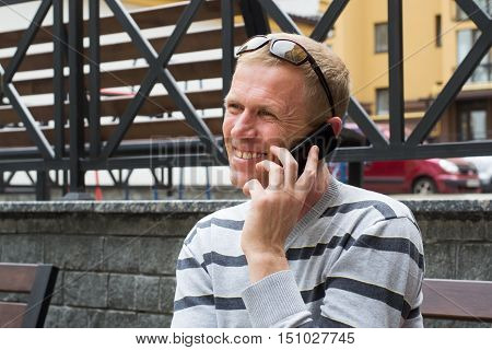 man on the street sitting on a bench with sunglasses in her hair is talking on a mobile phone