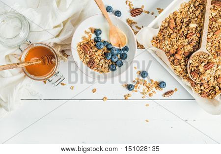 Healthy breakfast set. Oat granola with nuts, yogurt, honey and blueberries in bowl on white wooden background, top view, copy space, horizontal composition