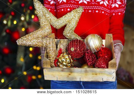 A woman holds a box with a lot of Christmas decorations near X-mas tree. Xmas holiday concept.