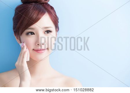 beauty skin care woman smile and make up on her face isolated on blue background asian