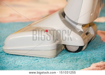 Close up of the head of a modern vacuum cleaner being used while vacuuming thick pile white carpet