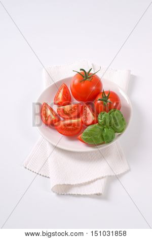 plate of whole and sliced tomatoes on white place mat