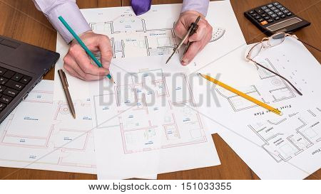 Architect working on blueprint with engineering worktools