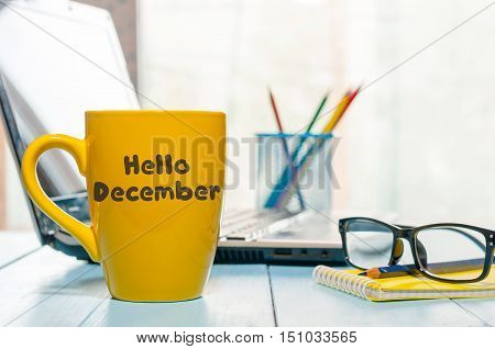 Hello December written on yellow coffee cup at manager or freelancer workplace. Eve, Christmas and New year time concept.